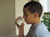 Bambino mentre beve un bicchiere di latte